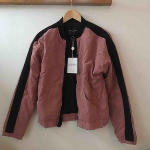 En helt ny rosa jacka med svarta detaljer från Rut & Circle, lappar kvar. Inköpt på na-kd.