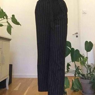 """Ett par randiga kostymbyxor med vida ben och snörning i midjan. Jätte fin passform, de är använda ganska mycket men fortfarande i mycket bra skick! Två """"fickor"""" för bak men de är inte riktiga. Byxorna slutar ungefär vid anklarna på mig som är 175cm💙"""