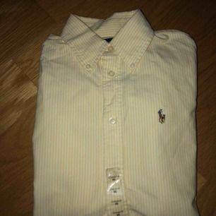 Gul-vitrandig Ralph Lauren skjorta, aldrig använd med prislappen kvar! Därav nyskick. Frakt tillkommer!