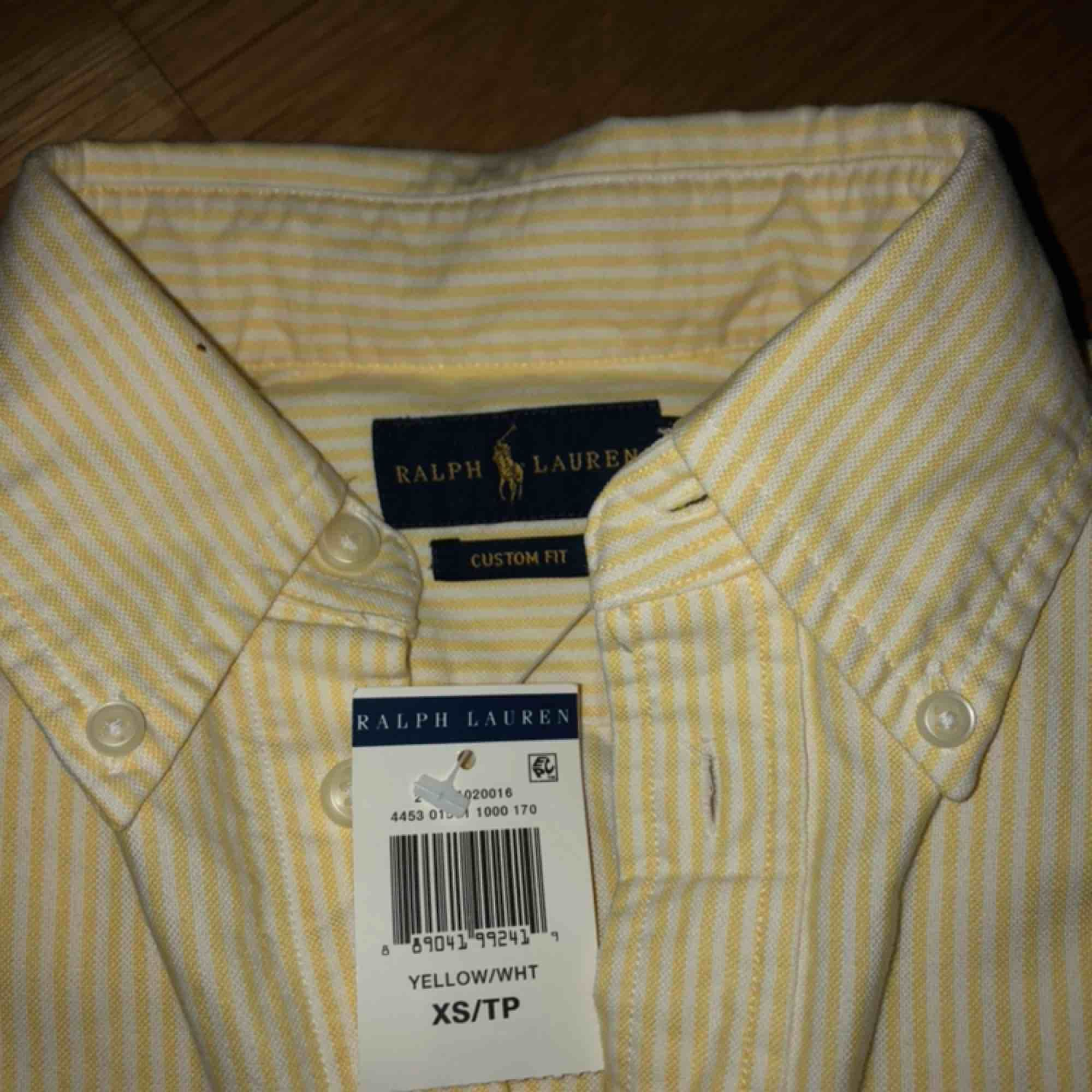 Gul-vitrandig Ralph Lauren skjorta, aldrig använd med prislappen kvar! Därav nyskick. Frakt tillkommer! . Skjortor.