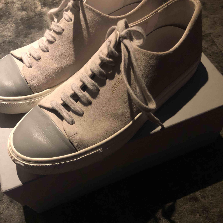 Jättesnygga Axel Arigato Cap toe sneakers storlek 38. Använda ett fåtal gånger därav är dem i väldigt bra skick. Kartong och dustbag ingår! Köptes för ca 1200kr. Skor.