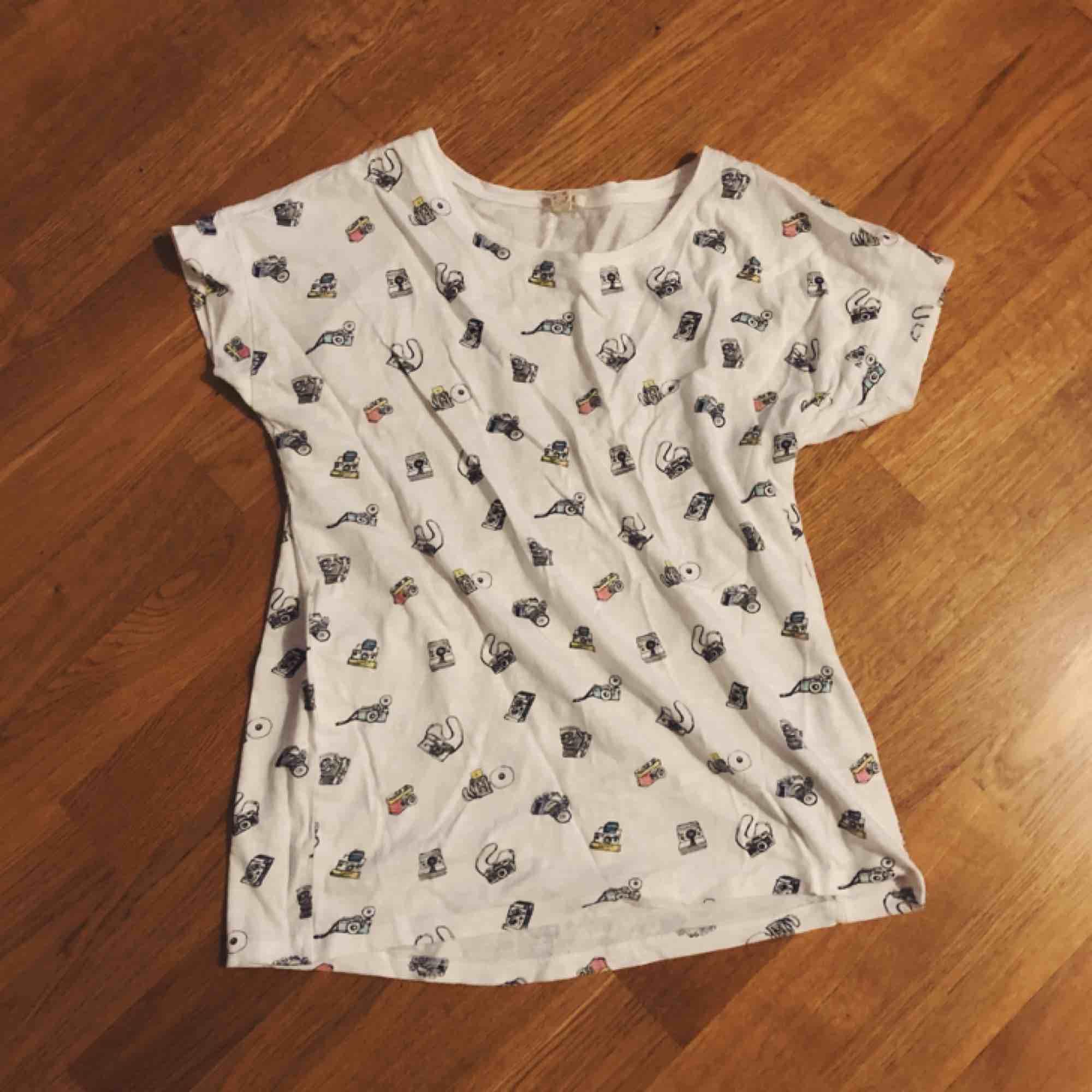 Jättesöt vit t-shirt med små kameror! Köparen står för frakt (42kr) eller mötas upp i Karlstad 💕. T-shirts.