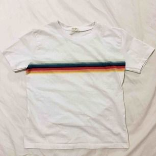 T-Shirt från Brandy Melville Beskrivning på hemsidan:  Soft cotton blend tee in white with rainbow stripes around the body and a white ringer collar. ca. 45 cm in width, ca. 55 cm in length Material: 100% cotton. Made in China.