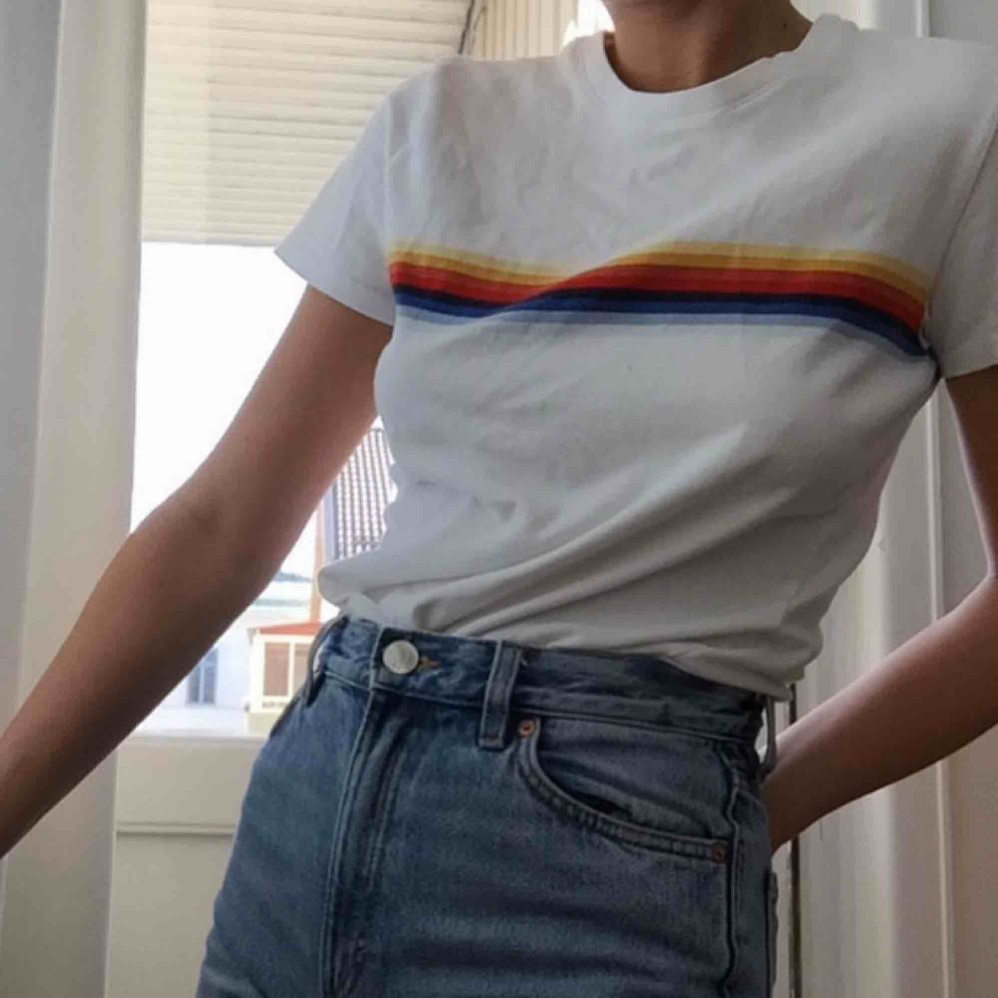 T-Shirt från Brandy Melville Beskrivning på hemsidan:  Soft cotton blend tee in white with rainbow stripes around the body and a white ringer collar. ca. 45 cm in width, ca. 55 cm in length Material: 100% cotton. Made in China.. T-shirts.