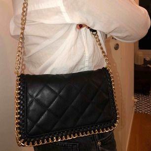 Super fin svart väska med en guldig kedja. Rymlig och går även att förlänga axelbandet.