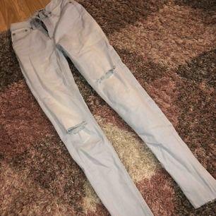 Snygga ljusblåa jeans med hål i