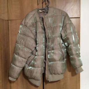 Vinterjacka från H&M TREND. Knappt använd.  Beige/grå i färgen. Med holografisk effekt.  Möts helst upp vid köp. Med fördel i Uppsala.