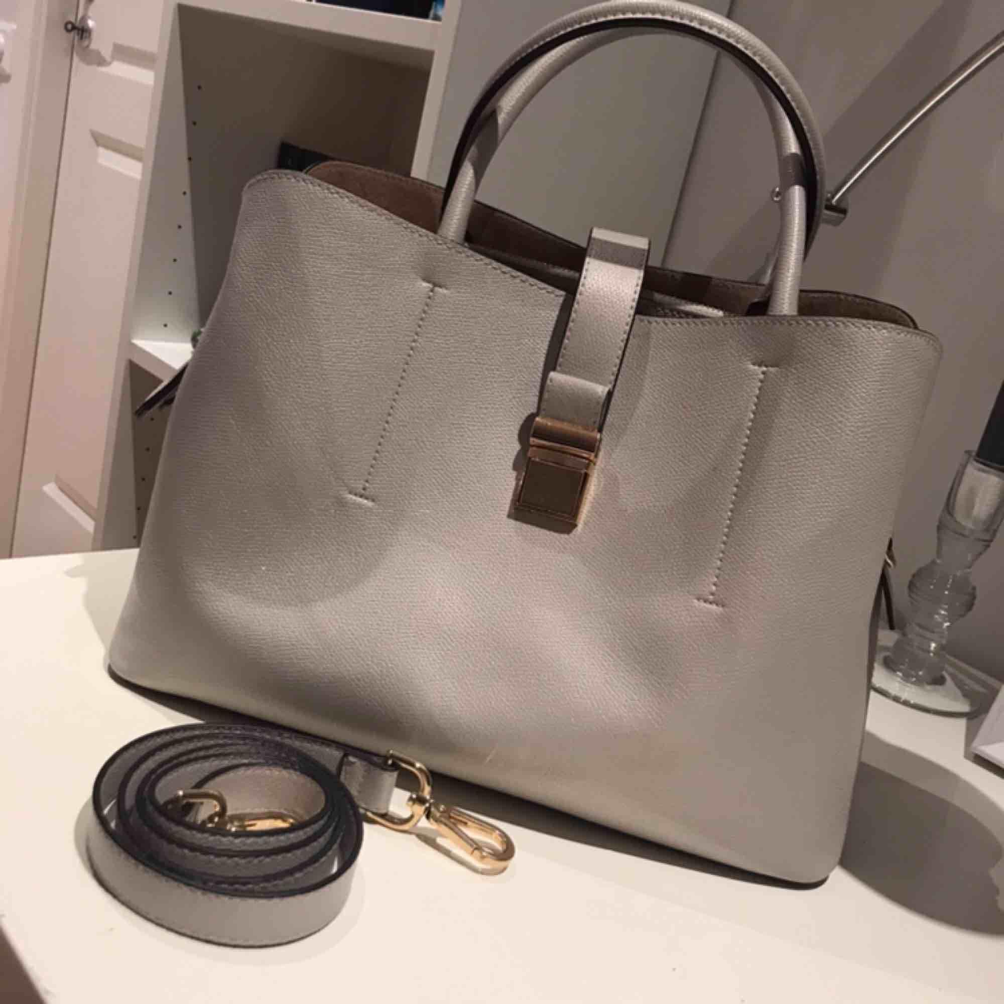 Fin grå väska med gulddetaljer. Den kan se glittrig ut på bilden, det är den inte. . Accessoarer.