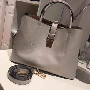 Fin grå väska med gulddetaljer. Den kan se glittrig ut på bilden, det är den inte.