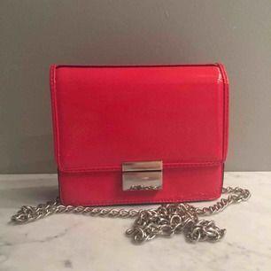 Fin röd lackad väska i bra skick! 16,5 x 13,5 cm med silverdetaljer. Kedjan är ca 140cm lång alltså crossbody väska! ☺️