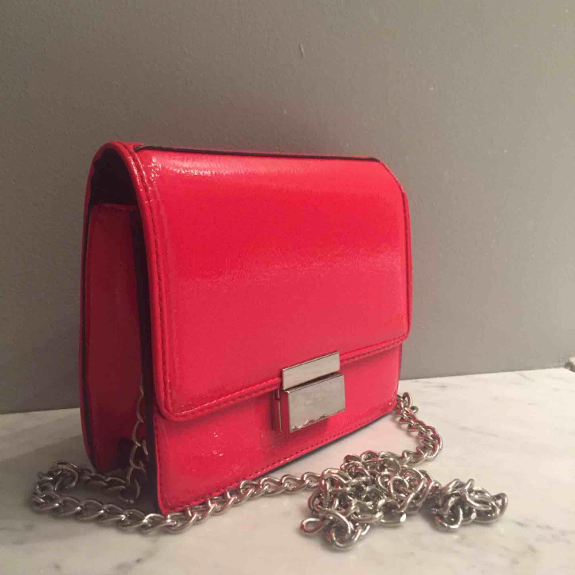 Fin röd lackad väska i bra skick! 16,5 x 13,5 cm med silverdetaljer. Kedjan är ca 140cm lång alltså crossbody väska! ☺️. Väskor.