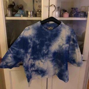 Säljer en T-shirt med tie dye mönster som är avklippt