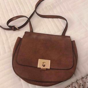 Brun praktisk handväska med guld detalj och innerficka
