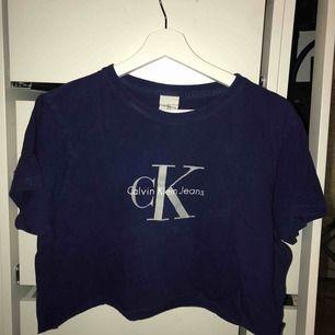 """En croppad blå tshirt från Calvin Klein. På tröjan står storlek """"XL"""" men då antar jag att det är barn XL då den sitter som en lite pösigare S."""