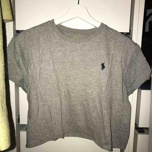 Grå croppad tshirt från Ralph Lauren. Det står storlek L i tröjan men den passar som en S/M och är inte helt formad till kroppen då.
