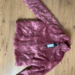 Fake-päls jacka i en underbar rosa färg! Köpte fel storlek så den är aldrig använd, så den är i nyskick! Färgen på jackan syns bäst på första två bilderna, ljuset på sista bilden är lite mörkt. Nypris 899kr, mitt pris 400kr. Frakt tillkommer😊