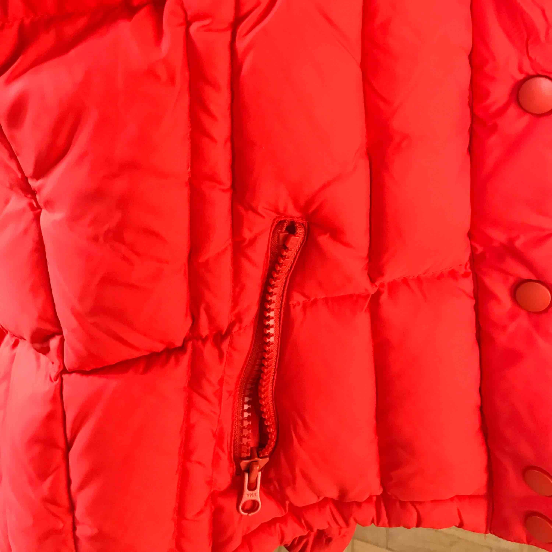 Röd väst från Björn Borg. Har luva och dubbla fickor. . Jackor.