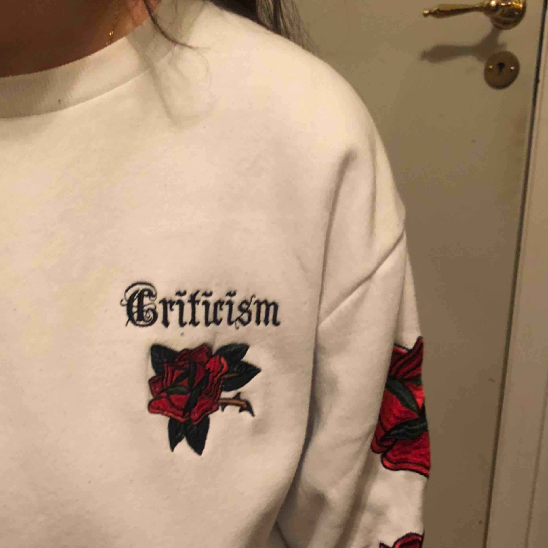 knappt använd fin vit sweatshirt med rosor längs armen, även en liten text i bak vid nacken. Huvtröjor & Träningströjor.