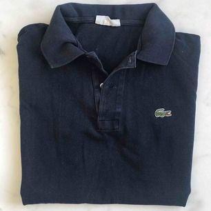 Äkta Lacoste-tröja. Köpt år 1985, så därav är den väldigt vintage. Storleken är 5 vilket motsvarar L, men kan ju knytas i midjan. En ny liknande tröja kostar idag 999kr. Skick 9/10. Tillkommer frakt på 59 kr.