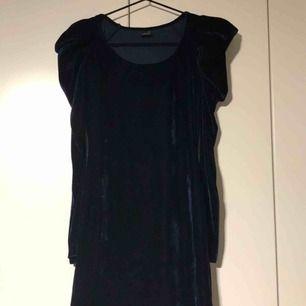 Fodralklänning i sammet midnattsblå med axelvaddar. Köpt på Gina Tricot. Jag är 170 cm och klänningen slutar en liten bit ovanför knänen.