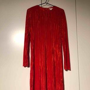 Röd cocktailklänning pilserad. Köparen står för frakten. Jag är 170 cm lång och den slutar alldeles under knät på mig.