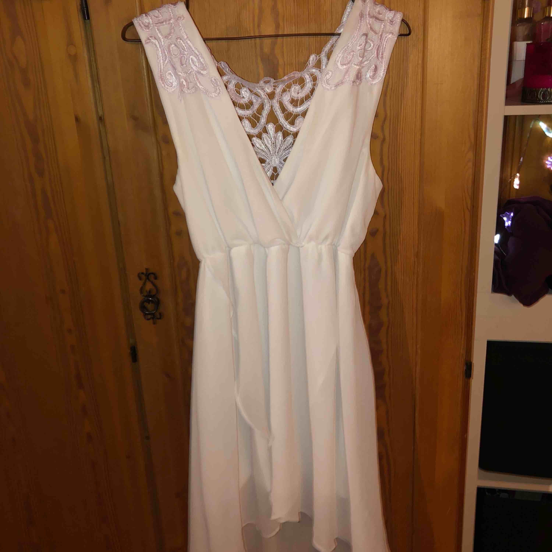 En vit klänning med lila spets på ryggen, använd en gång. Klänningar.