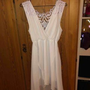 En vit klänning med lila spets på ryggen, använd en gång
