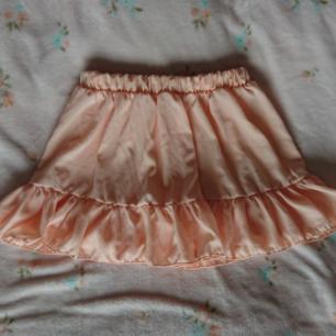 Supersöt persikorosa kort kjol med volang  Onesize, resår i midjan, fint skick  Rökfritt hem men har katter. Kan skickas men då står du för frakten.