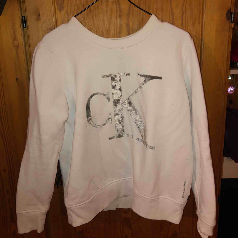 En vit tjocktröja från Calvin Klein, använt några gånger, dock har den en rönnbärsfläck på högra axeln som knappt syns i verkligheten men den finns där, har försökt att få bort den så många ggr men går inte . Tröjor & Koftor.