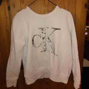 En vit tjocktröja från Calvin Klein, använt några gånger, dock har den en rönnbärsfläck på högra axeln som knappt syns i verkligheten men den finns där, har försökt att få bort den så många ggr men går inte