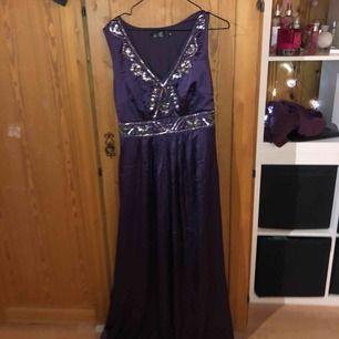 """En lila långklänning med """"diamanter"""" och pärlor upptill bysten, använt 1 gång i storlek 40/L från BPC selection"""