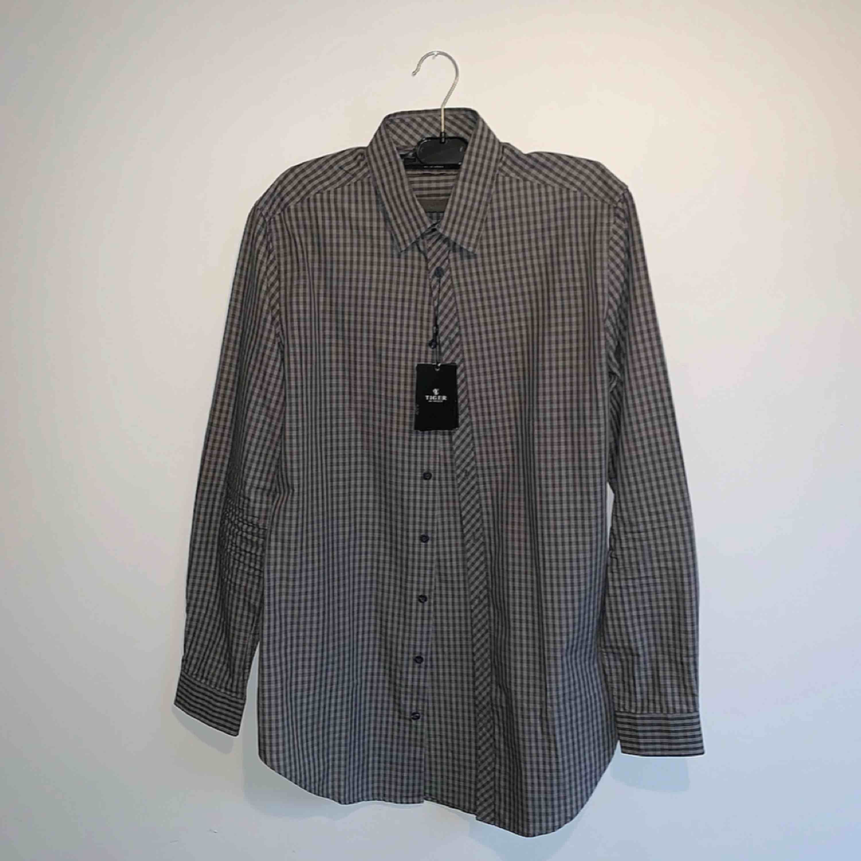 Gråsvart slim fit / long line skjorta från Tiger Of Sweden. Aldrig använd endast provad med prislapp kvar på.  Skick 10 / 10. Ord pris 999kr.. Skjortor.