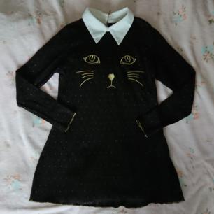 Supersöt klänning med misse, krage och gulddetaljer!  Står ingen storlek men uppskattar att den passar XS-S bäst.  Begagnat men fint skick  Rökfritt hem men har katter. Kan skickas men då står du för frakten.