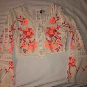 Mycket fin vit tröja med rosa/korallfärgade blommor i storlek 38 som säljs för 70kr! Den är lite öppen längst med ärmarna samt i mitten på framsidan