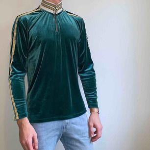 Långärmad t-shirt/polo från ASOS med hög krage och dragkedja i grön velour. Väldigt sparsamt använd. Skick: 8 / 10. Ord pris: 350kr