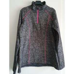 Träningströja/jacka i svart/grå melerat stretchigt lite tjockare tyg med rosa detaljer. Strl M, 40/42. Använd endast ett fåtal ggr. Fint skick.