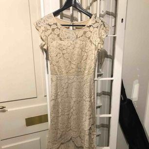 Vacker beige spetsklänning som är kortare fram & längre bak.  Klänningen har vaddering i byst. Finns även dragkedja i rygg. Klänningen har ett fastsytt underlinne. Storlek S/M - passar en small eller en liten medium. Använd en gång.
