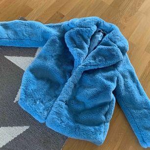 Letar du efter den perfekta jackan till höst och vinter? Den här fuskpälsjackan i en babyblå färg gör varje mörk dag härlig! Jackan är oanvänd och därför i nyskick!  Frakt 95 kr