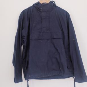 Snygg marinblå jacka från Urban Outfitters I pullover modell. Kardborre upptill, luva +fickor. Använd en gång. Kommer självklart tvättas + håras av innan den skickas. Köparen står för frakten 🌠