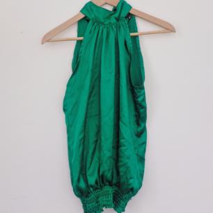 Grön, silkig blus från New Yorker. Hög krage som knyts i nacken, åtdragen nertill. Fint skick.  Köparen står för frakten 🌠
