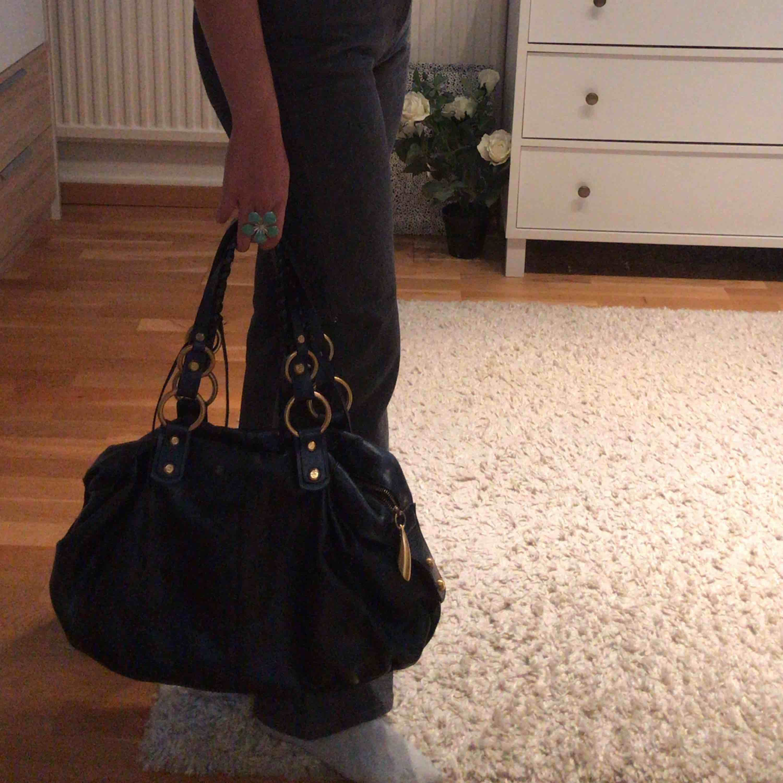Mörkblå väska med Guldiga detaljer, så snygg. Väskor.