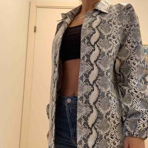 Pris inkl frakt. Skinnjacka med ormtryck, jackan har fickor och knappar till att stänga. Är köpt från fashionnova.