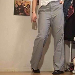 Ett par riktigt najs kostymbyxor som är vit och grå randiga. Passar både för M/L beroende på hur man vill att dem ska sitta. Jag är vanligtvis en  S/M  och då sitter dem mer oversize i modellen.