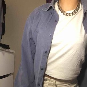 En snygg blå/grå skjorta i Manchester material. Har används flitigt men är fortfarande i bra skick, förutom ett litet hål vid en knapp (som ni ser på bilden) därför kan jag gå ner i pris vid snabb affär!