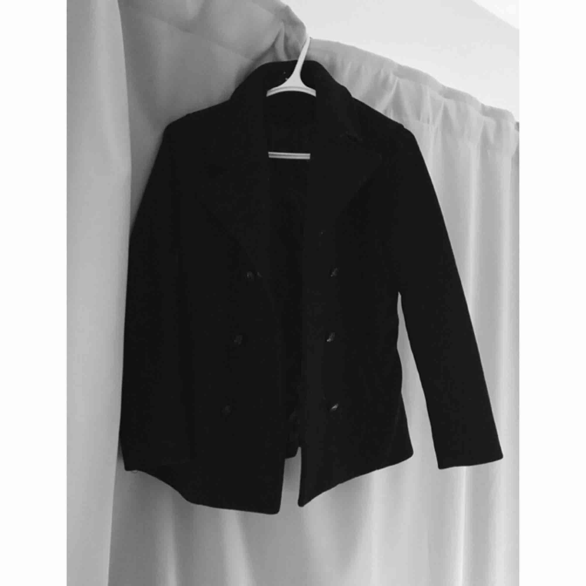 Elegant svart kappa/rock i kortare längd. Inköpt från Nelly. Använd ett par gånger men är i mycket bra skick. Perfekt i höst och vinter med en fin halsduk till. . Jackor.