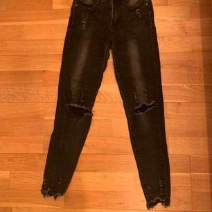 Mörkgrå jeans med hål i knäna och slitningar vid anklarna från Tessie i Göteborg. Väldigt stretchiga och sitter väldigt snyggt.