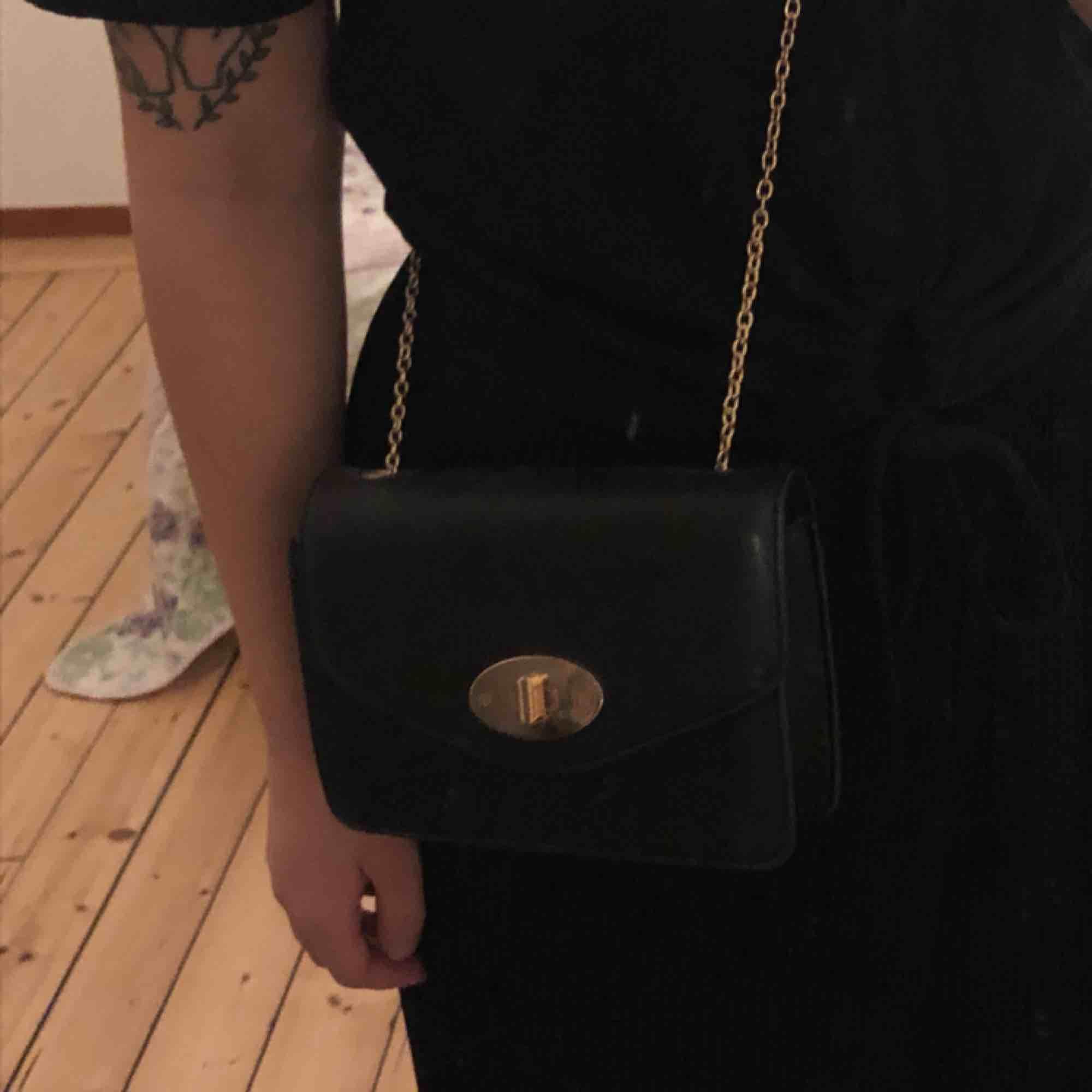 Finfin stilren väska med gulddetaljer! Kedjan går att stoppa in för att skapa en handväska istället för axelväska. Köpt på glitter och använd endast en gång. Möts upp i Sthlm, annars står köparen för frakten. 💛. Väskor.
