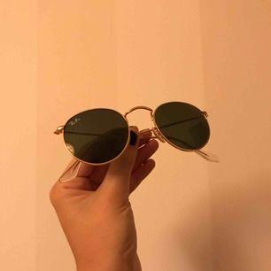 Unisex solglajjor från Rayban i modellen Round Metal. Har mörkgrönt glas och en guldkant längs hela solglasögonen. MYCKET sparsamt använda! Ordinarie pris 1300 kr, kan mötas upp i Linköping annars står köparen för frakt! 🤩