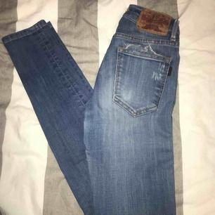 Högmidjade tajta jeans i strl 23/30. Använda ett flertal gånger men passar tyvärr inte längre. Lappen har dock gått upp på ena sidan (bild 2)