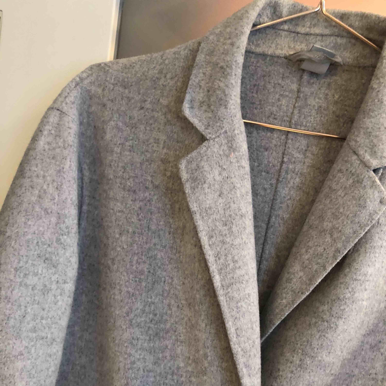 Snygg kappa i ljusgrå fleece med svarta knappar och två stora fickor. Den är varm och skön och är perfekt nu till vintern.  Köparen betalar frakt. . Jackor.